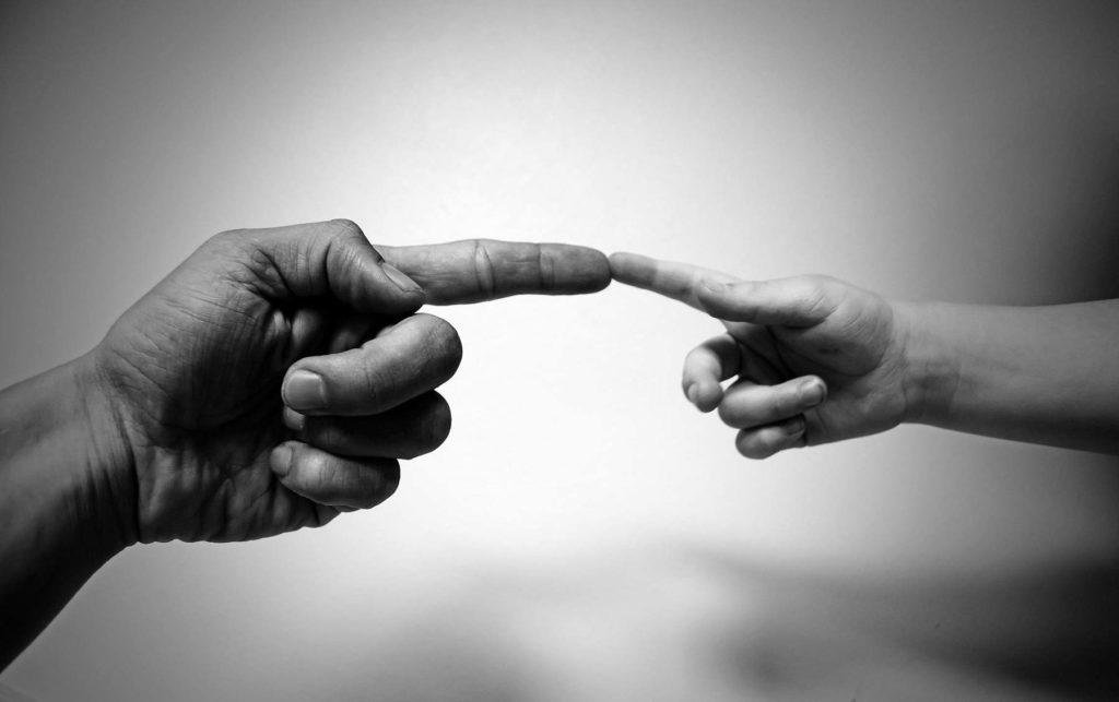 Photo de deux mains se rejoignant à la manière de Michelangelo